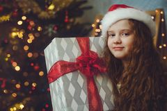 Eautiful little girl with gift and in Santa hat. royalty free stock photos