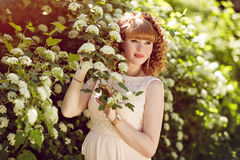 Eautiful red-haired and curly pregnant girl looks against the gr Royalty Free Stock Photos
