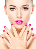 Eautiful woman face with pink makeup of eyes and nails. Royalty Free Stock Images