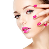 Eautiful woman face with pink makeup of eyes and nails. Royalty Free Stock Image