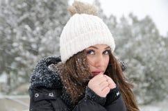 Βeautiful woman while its snowing with freezing hands Royalty Free Stock Images