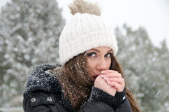 Βeautiful woman while its snowing with freezing hands. Portrait of beautiful young woman outside while its snowing, wear heavy jacket and white winter cap. Her Royalty Free Stock Photography