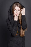 Иeautiful woman with long, gorgeous dark blond hair. She is dressed in warm gray knit dress with a hood. Stock Photos