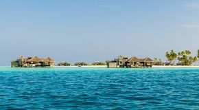Вeautiful wooden villas, standing on stilts in the turquoise waters of the Indian Ocean, Maldives. Вeautiful wooden villas, standing on stilts on little island Royalty Free Stock Photo