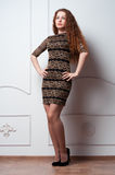 Eautiful young woman in dress stands near wall Royalty Free Stock Photo
