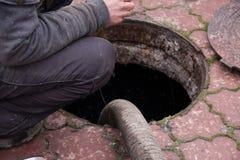 Eaux d'égout de pompage d'homme du trou de drain Photo libre de droits