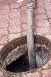 Eaux d'égout de pompage du trou de drain Photographie stock