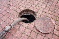 Eaux d'égout de pompage du trou de drain Photo libre de droits