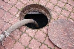 Eaux d'égout de pompage du trou de drain Images stock