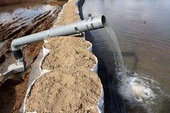 Eaux d'inondation de pompage de pompe à eau au-dessus des barrières de bac à sable par le grand tuyau en métal images libres de droits