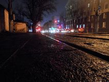 Evening streets at small town. Eavening streets at small town. Big tree, houses, tram rails, lights, traffic royalty free stock photography