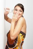 Eaves-dropping. Beautiful young woman, elegantly dressed eaves-dropping by holding glass to the wall - laughing Stock Photo