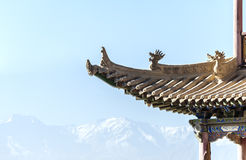 Eaves of a tower in Jiayuguan against distant snow-capped mounta Royalty Free Stock Photo