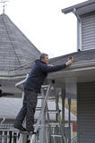 Eaves trough Cleaning - Home Maintenance. A homeowner tackles the chore of cleaning out the eaves troughs during late fall Stock Photos