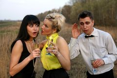 Eavesdropping of secrets. Two girl and man with wine outdoors Royalty Free Stock Image