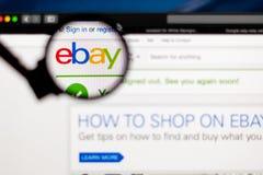 Ebay-bedrijfembleem zichtbaar door een vergrootglas stock foto