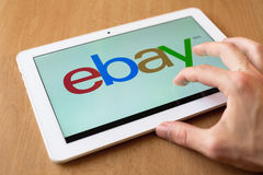 Ebay. Man's hand use with his fingers tablet. Ebay app is on the screen. Ebay provides consumer-to-consumer and business-to-consumer sales royalty free stock images