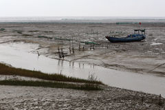 After the ebb, the boat ran aground on the tidal flat river of mud, Royalty Free Stock Image