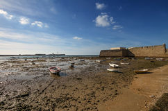 Ebb in Cadiz. Boats in Cadiz harbor with low tide. Spain, Andalusia Stock Photos