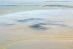 Ebb-tide in Normandy. Ebb-tide in Mont Saint-Michel (Normandy) at the north coast of France.  The rocky island is during the ebb-tide an peninsula Royalty Free Stock Photo