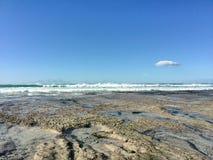 Ebbe deckt Felsen und Gezeitenpools am Seeufer auf Stockfoto