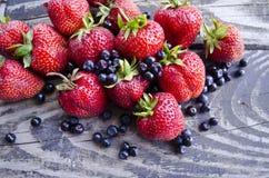 Eben gesammelte frische Blaubeeren und Erdbeeren auf hölzernem Hintergrund Sommer-organische Beere über Holz Stockfotos