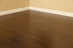 Eben installierter Brown-Laminats-Bodenbelag und Fußleisten im Haus Stockfotos