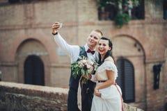 Eben verheiratete Paare, die selfie nach Zeremonie machen lizenzfreie stockfotografie