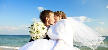 Eben verheiratetes Paar, das auf dem Strand küßt. Stockbild