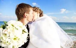 Eben verheiratetes Paar, das auf dem Strand küßt. Stockbilder
