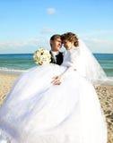 Eben verheiratetes Paar, das auf dem Strand küßt. Lizenzfreies Stockbild