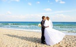 Eben verheiratetes Paar, das auf dem Strand küßt. Lizenzfreies Stockfoto