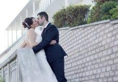Eben verheiratetes Paar, das draußen küsst Stockfotografie