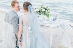 Eben verheiratetes Paar, das Hochzeit durch das Meer zu Abend isst stockfoto