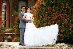 Eben verheiratetes Paar, das im schönen Garten aufwirft Lizenzfreie Stockbilder