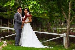 Eben verheiratetes Paar, das im schönen Garten aufwirft Stockfotos