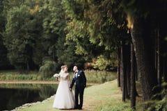 Eben verheiratetes Paar, das in Park während Händchenhalten läuft und springt stockfoto