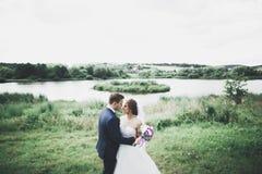 Eben verheiratetes Paar, das in Park w?hrend H?ndchenhalten l?uft und springt lizenzfreie stockfotografie