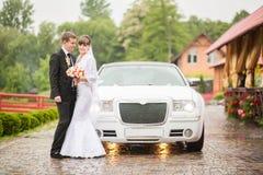 Eben verheiratetes stehendes nahes Hochzeitsauto Lizenzfreie Stockfotos