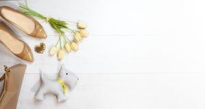 Ebene gelegtes weibliches Ausstattungssammlungskleid: beige Schuhhandtaschenzusatzgoldherztulpen und Spielzeughund auf weißem höl stockbild