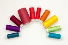 Ebenenlage mit bunten Baumwollfadenspulen, Stickgarn, Regenbogenspulen, Spott oben, Draufsicht Planmodell auf leerem Wei? lizenzfreies stockfoto