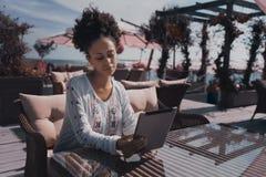 Ebenholtssvart kvinnlig med den digitala minnestavlan i det utomhus- kafét Arkivbilder