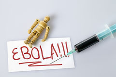 Ebola concept with a wooden figure and blood filled syringe Stock Photography