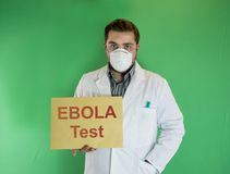 Ebola test. Young doctor with mask holding Ebola Test sign Stock Images