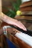 Ebony and Ivory Harmony. One older white hand and one younger black hand playing the piano Stock Image