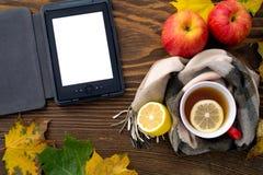 EBook和一个杯子热的茶用在一张木桌上的一条围巾包裹的柠檬 免版税图库摄影