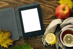 EBook和一个杯子热的茶用在一张木桌上的一条围巾包裹的柠檬 免版税库存照片