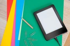 Ebook που χρεώνει σε χαρτιά χρωμάτων με το μολύβι και τους συνδετήρες στοκ εικόνες