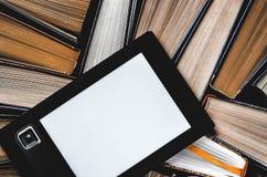 EBook с белым экраном лежит на открытых пестротканых книгах которые лежат на темной предпосылке, конце-вверх стоковое изображение