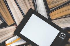 EBook с белым экраном лежит на открытых пестротканых книгах которые лежат на темной предпосылке, конце-вверх стоковая фотография rf